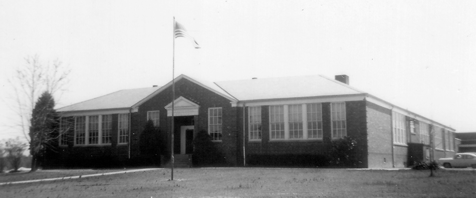 Black and white photograph of the original main entrance of Franconia Elementary School taken in 1954 for the Fairfax County School Board's Fire Insurance Survey. A flagpole in visible in front of the building and several additions can be seen to the rear of the building on the far right of the image. Also on the far right is an early 1950s car.