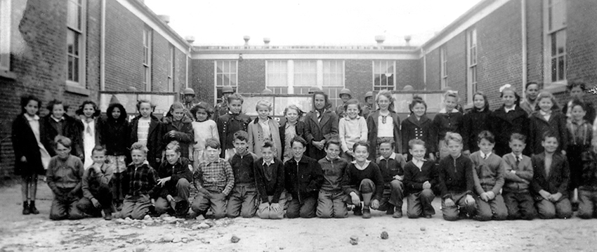 Black and white class photograph of children at Franconia Elementary School. The front row, all boys, are kneeling. Behind them stands a row of girls. The children are wearing coats and sweaters and look to be about 10-years-old. Behind them are U.S. Army soldiers sitting in jeeps. The picture was taken during the World War II timeframe, exact date unknown, but it appears to have been a visit to the school by soldiers and the photograph was taken to commemorate the occasion.