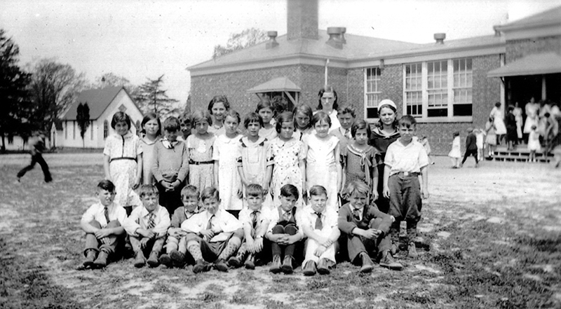 Black and white class photograph of a group of children with their teacher. The picture was taken outside the back of the original Franconia Elementary building as it appeared in 1932. A small church is visible in the distance. The building has had no additions constructed. Another group of children can be seen entering through a door in the rear of the building. The children in the photo appear about 10-years of age. The boys are seated on the ground and the girls and teacher stand behind them. The girls are wearing dresses and the boys are wearing short-sleeved shirts with ties so the picture was taken during warm weather.