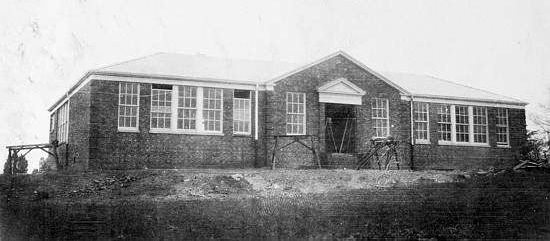 Black and white photograph of the original front entrance of Franconia Elementary School during construction in 1931. Workbenches and materials are visible in front of the building. The walls, windows, and roof are all in place.